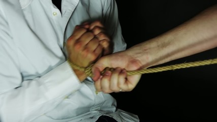 Binding rope on hands.
