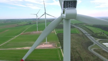 Windpark: green energy, windmill from behind, drone flight.
