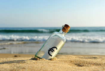 Bottle with euro sign on the beach