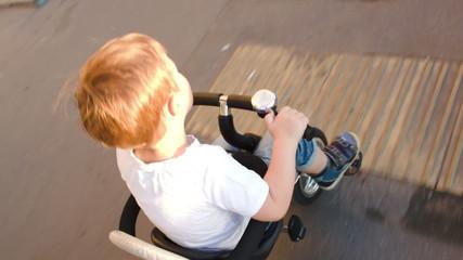 Little boy riding a bike quickly