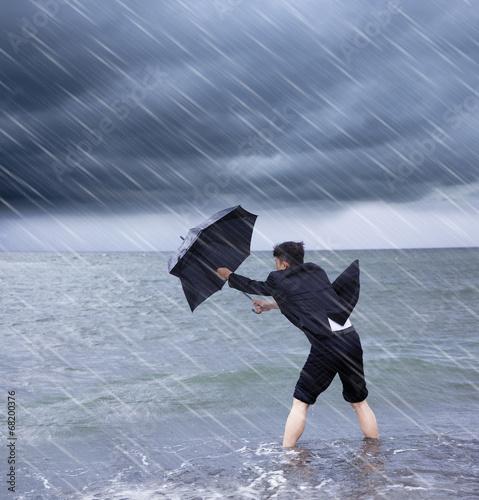 business man holding a umbrella to resist rainstorm