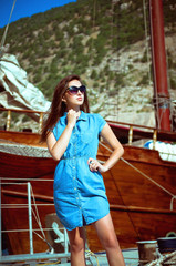 portrait of a girl near the sea on the background of a yacht