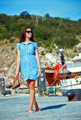 girl walks on the quay at the sea on a background of yachts