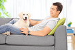 Young man sitting with his puppy on a sofa at home