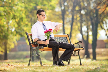 Young guy waiting for his date in park