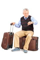 Senior tourist checking the time seated on his luggage
