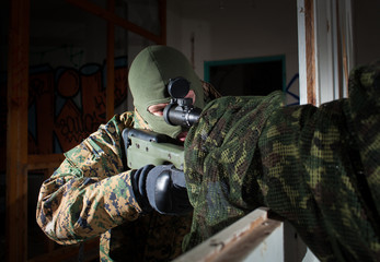 Masked sniper is aiming at the target during the mission