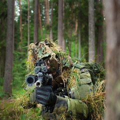 Masked soldier is aiming at the target during the mission (color