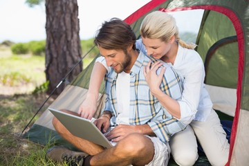 Attractive couple sitting by their tent using laptop