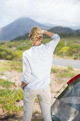 Attractive blonde standing by tent looking at mountain