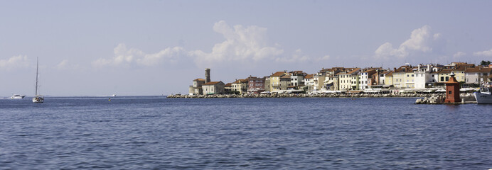 Piran town panorama with sailboat and a red lighthouse