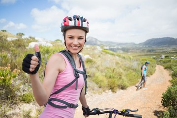 Fit couple cycling on mountain trail woman smiling at camera