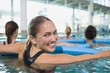 Happy fitness class doing aqua aerobics with foam rollers - 68202336