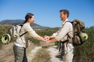 Hiking couple putting hands together on country trail