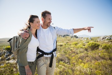Hiking couple pointing and smiling on country terrain