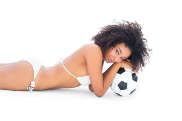Fit girl in white bikini holding football lying on floor