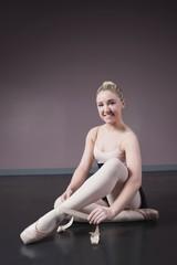 Pretty ballerina tying the ribbon on her ballet slippers