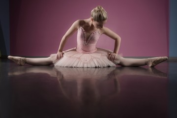 Graceful ballerina sitting with legs stretched out