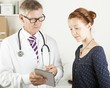doctor and a patient woman looking something on tablet pc