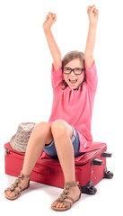 girl sitting on a suitcase is happy to go on holiday