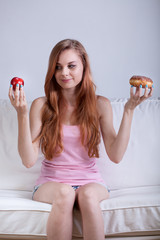 Girl prefering apple than donut