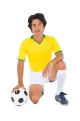 Football player in yellow kneeling with ball