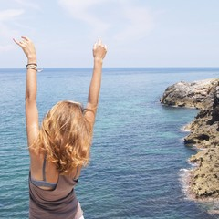 girl near the ocean with hands up