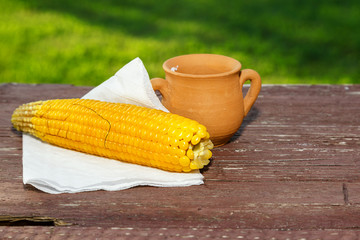 Cooked corn on wooden table in the garden