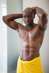 Muscular man wrapped in yellow towel