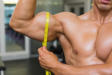 <id section of muscular man measuring biceps