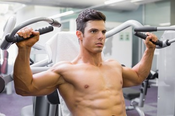 Muscular man working on fitness machine at the gym