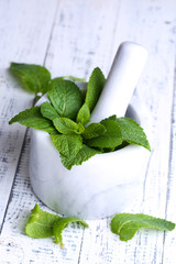 Fresh green mint in mortar on color wooden background