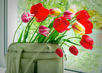 Flowers tulips and a women bag on a window window sill.