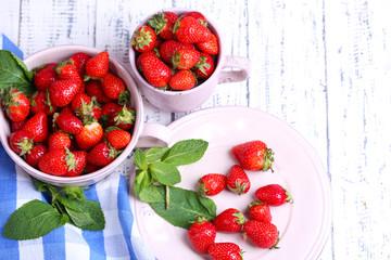 Ripe sweet strawberries in pot and mug