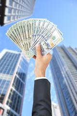 Hand raising money - United States Dollars (or USD)