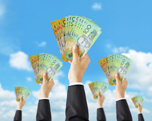 Hands holding money - Australian dollar (AUD) banknotes