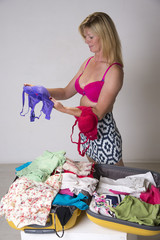 Woman packing clothes into a suitcase for holiday