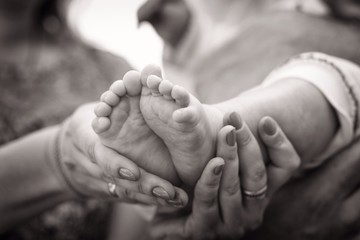 ножки малыша в руках матери