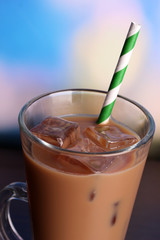 Glass of iced milk coffee on bright background