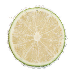 Fresh lime in water with bubbles, isolated on white