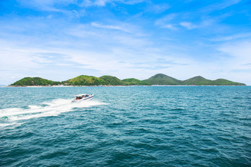 Tropical island and speed boat going to island
