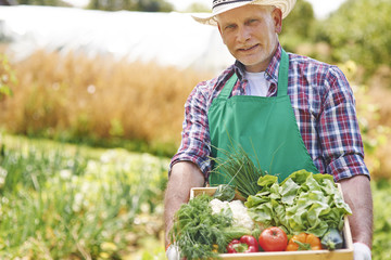 Portrait of proud man with his harvest in home garden