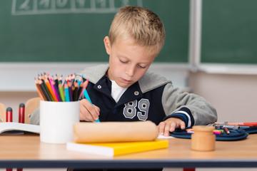 junge in der schule malt mit buntstiften