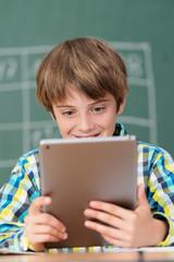 junge in der schule schaut auf tablet-pc