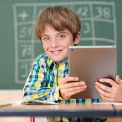 glücklicher schuljunge arbeitet mit tablet-pc