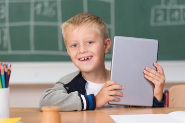 lachender junge hält tablet-pc in händen