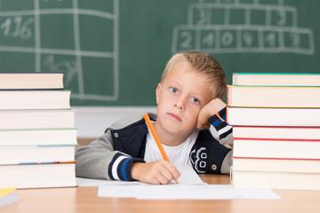 grundschüler sitzt müde zwischen schulbüchern