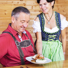 Woman in traditional Bavarian Tracht serves one white sausages