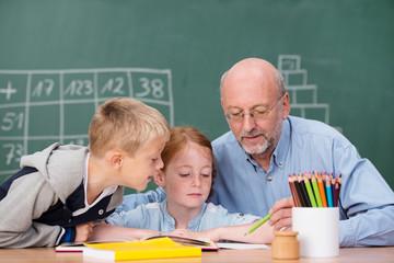 lehrer erklärt kinder etwas im unterricht
