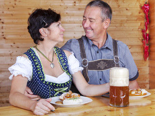 Man and woman in bavarian costume at the snack